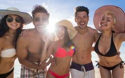 Ungdomargrupp på strandsommarsemester, lycklig le vänsjösidaCloseup arkivbilder