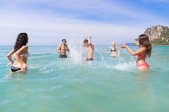 Ungdomargrupp på strandsommarsemester, lyckliga le vänner i vattenhavshavet Fotografering för Bildbyråer