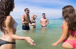 Ungdomargrupp på strandsommarsemester, lyckliga le vänner i vattenhavshavet Royaltyfria Bilder