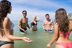 Ungdomargrupp på strandsommarsemester, lyckliga le vänner i vattenhavshavet Arkivfoto