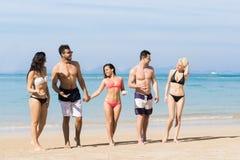 Ungdomargrupp på strandsommarsemester, lyckliga le vänner som går sjösidahavshavet Arkivbilder
