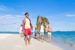 Ungdomargrupp på strandsommarsemester, lyckliga le vänner som går sjösidan Arkivfoto