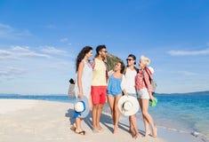 Ungdomargrupp på strandsommarsemester, lyckliga le vänner som går sjösidan Royaltyfria Foton