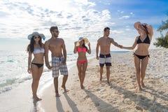 Ungdomargrupp på strandsommarsemester, lyckliga le vänner som går sjösidan Royaltyfri Bild