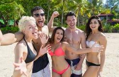 Ungdomargrupp på strandsommarsemester, lyckliga le vänner som tar havet för Selfie fotohav Arkivfoton