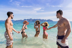 Ungdomargrupp på strandsommarsemester, vänner i vattensjösida Arkivfoto