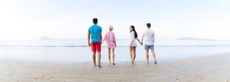 Ungdomargrupp på strandsommarsemester, vänner som går tillbaka bakre sikt för sjösida Arkivfoto