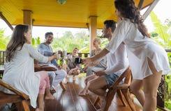 Ungdomargrupp som har frukosten på det tropiska hotellet för terrass, semester för vänvändkretsferie Royaltyfria Foton