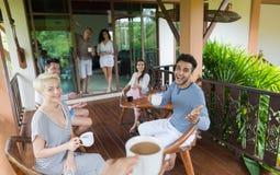 Ungdomargrupp som har frukosten på det tropiska hotellet för terrass, semester för vänvändkretsferie Arkivfoton