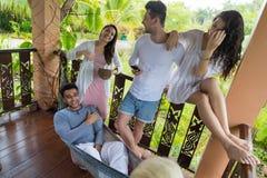 Ungdomargrupp som talar på tropiskt hotell för terrass, semester för vänvändkretsferie Royaltyfria Bilder