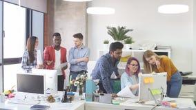 Ungdomargruppen i modernt kontor har diskussion av ett nytt projekt stock video