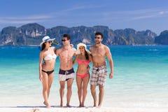 Ungdomargruppen på strandsommarsemester, två kopplar ihop lyckliga le vänner som går sjösidan Arkivbilder