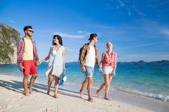 Ungdomargruppen på strandsommarsemester, två kopplar ihop lyckliga le vänner som går sjösidan Arkivbild