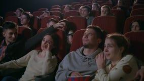 Ungdomarhållande ögonen på film i bio Romantiskt datum på bion stock video