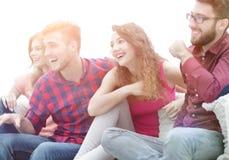 Ungdomarhåller ögonen på ditt favorit- showsammanträde på soffan arkivbild
