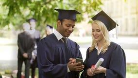 Ungdomari den doktorand- likformign som ser telefonskärmen och att ha diskussionen, jobb royaltyfria foton