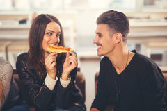 Ungdomari tillfällig kläder som äter pizza arkivfoto