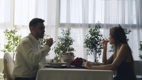 Ungdomarklirrar dricker lyckliga par exponeringsglas och champagne på romantiskt datum i dyr restaurang roman arkivfilmer