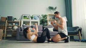 Ungdomarman och kvinna som gör situpsen och applåderar händer som hemma utbildar lager videofilmer