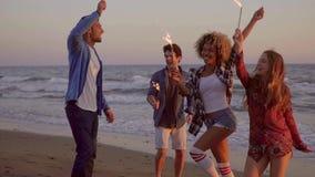 Ungdomarmed springbrunnstearinljus på stranden arkivfilmer