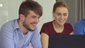 Ungdomarskrattar på tabellen med bärbara datorn arkivbilder