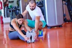 Ungdomarsom är involverade i sportar Kvinna som sträcker med den personliga instruktören Royaltyfri Bild