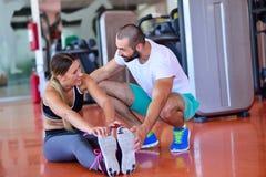 Ungdomarsom är involverade i sportar Kvinna som sträcker med den personliga instruktören Royaltyfria Bilder