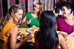 Ungdomarsom äter i restaurang Fotografering för Bildbyråer