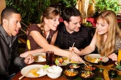 Ungdomarsom äter i thailändsk restaurang fotografering för bildbyråer