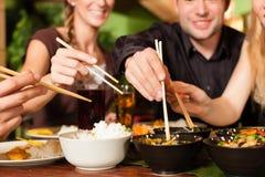 Ungdomarsom äter i thailändsk restaurang arkivbild