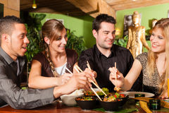 Ungdomarsom äter i thailändsk restaurang royaltyfria foton