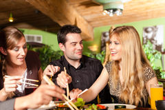 Ungdomarsom äter i thailändsk restaurang royaltyfri foto