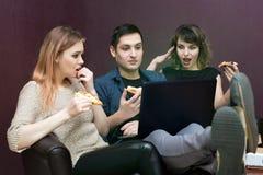 Ungdomarsom äter pizza på bärbara datorn royaltyfria bilder