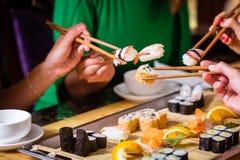 Ungdomarsom äter sushi i restaurang Fotografering för Bildbyråer