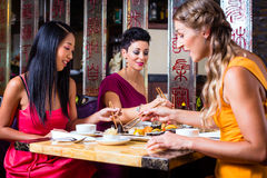 Ungdomarsom äter sushi i restaurang Royaltyfria Bilder