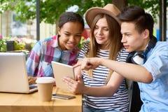 Ungdomarsom använder moderna apparater i kafé royaltyfri bild