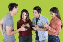 Ungdomarsom använder smartphonen på studio royaltyfri bild