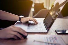 Ungdomarsom arbetar med den moderna bärbara datorn i arbetsplatsen, kafé Royaltyfri Foto