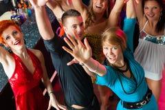Ungdomarsom dansar i klubba eller disko, män och kvinnor arkivfoto