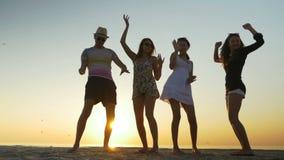 Ungdomarsom dansar på en strand på skymning lager videofilmer