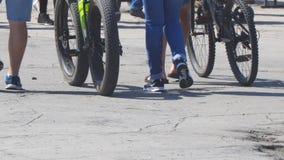 Ungdomarsom går på gatan med cyklar arkivfilmer