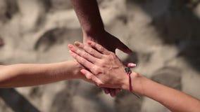 Ungdomarsom gör en bunt av händer på stranden stock video