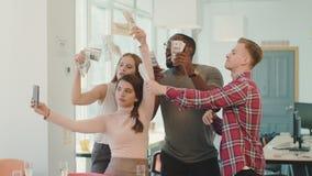 Ungdomarsom gör gyckel med pengar på coworking Lyckligt folk som tar selfie stock video