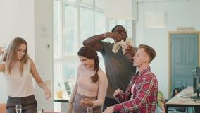 Ungdomarsom gör regn med pengar på coworking utrymme Pengarflyg i luft stock video