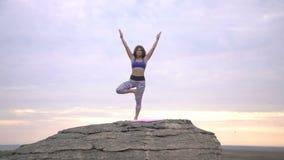 Ungdomarsom gör yoga på gryning arkivfilmer