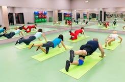 Ungdomarsom gör övningar i idrottshallen Royaltyfri Bild