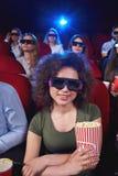 Ungdomarsom håller ögonen på filmen 3D på filmteatern Arkivbilder
