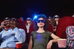 Ungdomarsom håller ögonen på filmen 3D på filmteatern Fotografering för Bildbyråer
