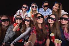 Ungdomarsom håller ögonen på filmen 3D på filmteatern royaltyfri bild