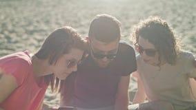 Ungdomarsom har gyckel på stranden genom att använda telefoner stock video